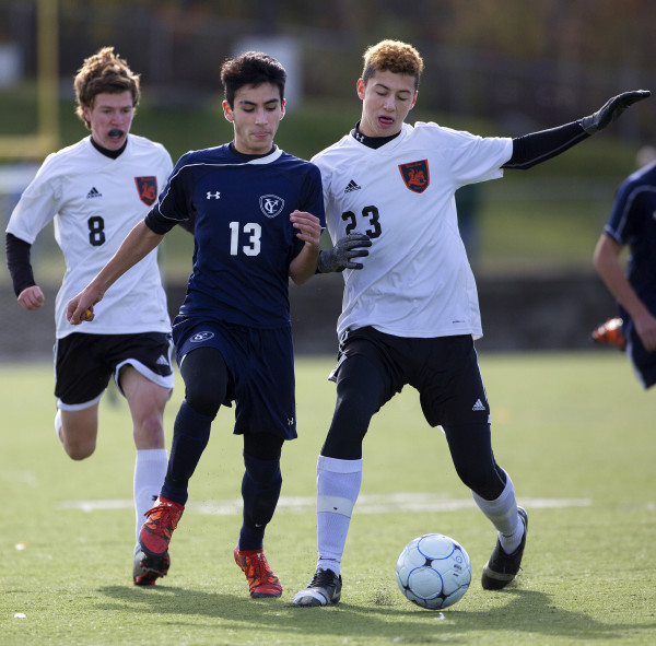 Yarmouth's Max Coury (left) and Winslow's Jackson Morneault battle for the ball during their Class B boys state championship soccer game at Hampden Academy Saturday.