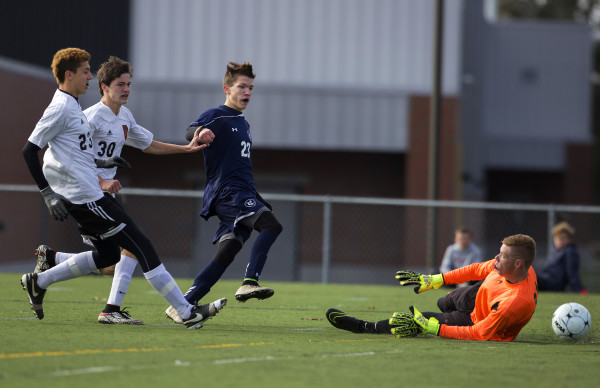 Yarmouth's Eric LaBrie (center) puts a shot past Winslow goalkeeper Jake Lapierre for a goal during their Class B boys state championship soccer game at Hampden Academy Saturday.