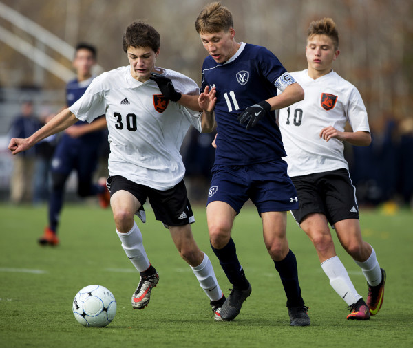 Yarmouth's Matthew Dostie (center) battles for the ball against Winslow's ___ and Michael Wildes during their Class B boys state championship soccer game at Hampden Academy Saturday.