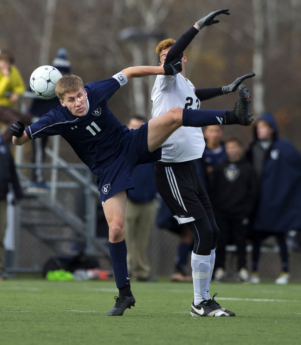 Yarmouth's Matthew Dostie (left) and Winslow's Jackson Morneault battle for the ball during their Class B boys state championship soccer game at Hampden Academy Saturday.