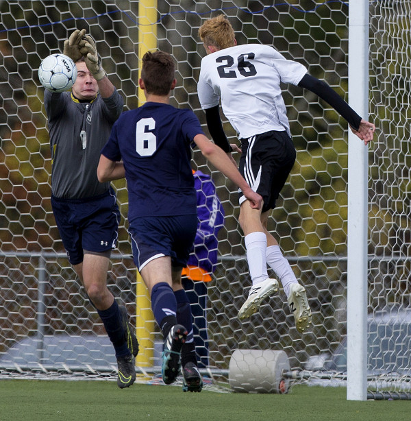Yarmouth's Michael Hagerty (left) makes a save before Winslow's Daylon Carpenter can get a head on it during their Class B boys state championship soccer game at Hampden Academy Saturday.
