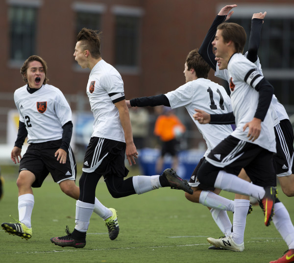 Winslow's Jake Warn (center) celebrates after scoring a goal against Yarmouth during their Class B boys state championship soccer game at Hampden Academy Saturday.