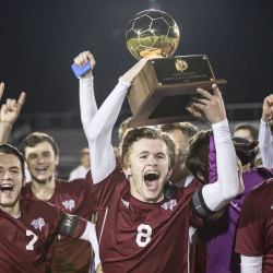 Bangor High School boy's soccer Captain Carson Atherley (center) hoists the gold ball after Bangor's win against Gorham High School 4-1 in a penalty kick shoot out during the Class A state championship game at Fitzpatrick Stadium in Portland on Saturday.