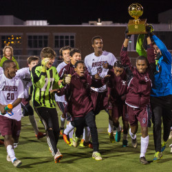 The Washington Academy boys soccer team runs across the field toward a cheering crowd with their Class C state championship trophy after a 5-1 win against the Monmouth Mustangs at Hampden Academy on Saturday evening.