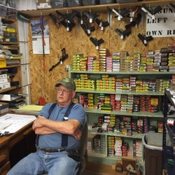Bob Berg, the owner of Bob & Tom's gun shop, sits behind the counter of his store in October.