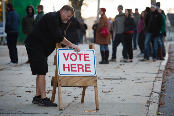 Jeff Hodgdon puts a sign out on the sidewalk as the polls open at the Portland Expo at 7 a.m. Tuesday in Portland.