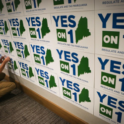 Nick Murray pins a sign to a wall at the Yes on 1 election night headquarters in Portland on Tuesday night.