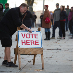 Jeff Hodgdon puts a sign out on the sidewalk as the polls open at the Portland Expo at 7 a.m. on Tuesday in Portland. About a hundred people waited in line.