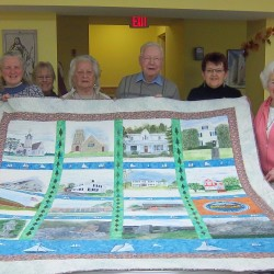 Artists and members of the Brewer Historical Society show off the hand-painted, queen-size quilt created by members of the Age(less) Artists group.The quilt, depicting historic scenes of Brewer, will be raffled to raise funds for repairing the roof of the 1898 First Congregational Church of Brewer, where the group of painters has been meeting since the closure last year of the Hammond Street Senior Center in Bangor.