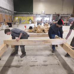 Kennebec Valley Community College timberframing instructor Sandor Nagy (second from left) gives pointers to students on the fitting of a floor joist in a timberframe structure. The college's sustainable construction program started two years ago. Also pictured are students Amber Oberle (right), Vinnie Birtwell (left) and Hannes Moll.