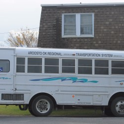 A bus from the Aroostook Regional Transportation System drops off a rider at an apartment in Presque Isle in late October.