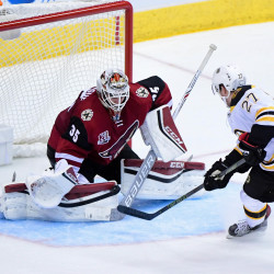 Arizona Coyotes goalie Louis Domingue (35) makes a save on Boston Bruins center Austin Czarnik (27) in the third period at Gila River Arena. The Bruins won 2-1.