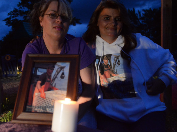 Leslie Perry (left) and Christi Woodruff, both of Corinna, brought a picture of Michael Ranke, who died of an overdose of heroin cut with the painkiller fentanyl, to a candlelight vigil on Aug. 31 in Lincoln.