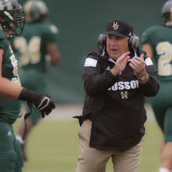 Husson University football coach Gabby Price congratulates his players in the first half of their college football game against Alfred State at Husson in Bangor, Sept. 20, 2014.