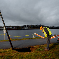 City worker Tobi Smith looks into a 10-foot-deep sinkhole underneath a section of sidewalk along the Banor Waterfront on Wednesday afternoon.