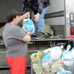 Samaritan Inc. Food Pantry volunteers Jeremy Lamarre (left) and Joe Sites, both of Bangor, load turkeys donated to area food pantries on Thursday in the Hannaford Supermarket parking lot in Brewer.