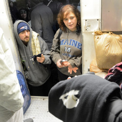 A volunteer at Jericho Road Street Ministry's clothing giveaway shows sweatpants to participants during the annual Thanksgiving dinner on Monday in Bangor.