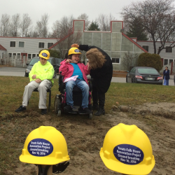 Treats Falls House resident Nye Ivers (center) laughs as a helper straightens her hardhat during the groundbreaking for a nearly $5 million renovation and expansion at the facility on Nov. 16 in Orono.