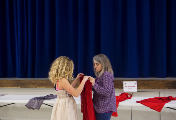 While wearing a possible dress selection, Madison Johnson (left), 11, looks over another dress with Hope Violette at the Bangor Housing Authority's community center in Bangor Wednesday. UsTrendy, an ecommerce site, donated 25 dresses.
