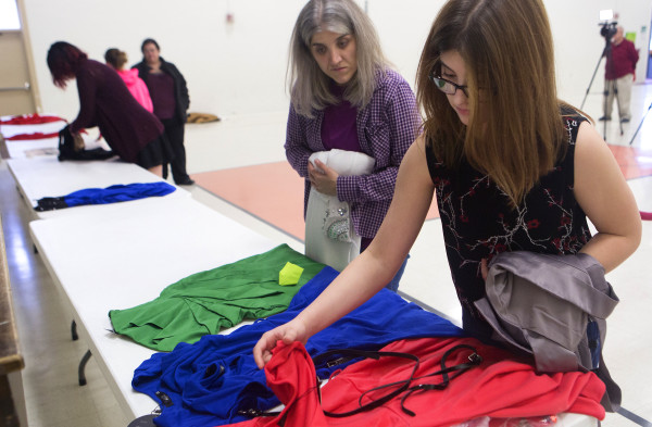 Jasmine Johnson (right), 14, browses a selection of dresses with Hope Violette at the Bangor Housing Authority's community center in Bangor Wednesday. UsTrendy, an ecommerce site, donated 25 dresses.