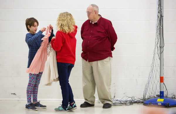 Madison Johnson (left), 11, looks over her dress she selected with Teeonna Ryder (center), 11, while Skip Ryder looks on at the Bangor Housing Authority's community center in Bangor Wednesday. UsTrendy, an ecommerce site, donated 25 dresses.