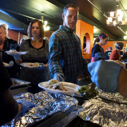 Bob Ogan (center) has plates filled with food to give to people during the inaugural Thanksgiving dinner at CityReach in Bangor Thursday. Following the free meal, guests were invited to watch football on two large televisions.