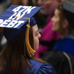 A graduate with their debt amount on their hat makes her way to the stage to receive her diploma during the 150th anniversary year graduation at the University of Maine in Orono, May 9, 2015.