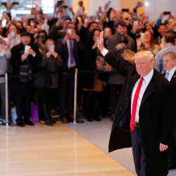 President-elect Donald Trump reacts to a crowd gathered in the lobby of the New York Times building after a meeting with the paper's editorial board on Nov. 22, 2016.