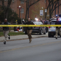 Officers run away from Watts Hall Monday, Nov. 28, 2016 during reports of an attacker on Ohio State's campus in Columbus, Ohio. Law enforcement sources say 10 people have been transported to hospitals and a suspect has been killed.