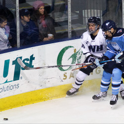 University of Maine hockey defenseman Rob Michel spars with a Wildcat from the University of New Hampshire as the two teams duked it out at the Cross Insurance Arena on Dec. 29, 2015, in Portland.
