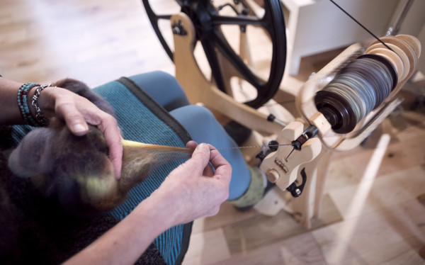 Jodi Clayton, owner of One Lupine Fiber Arts, demonstrates the use of a spinning wheel on Monday at her shop in Bangor.