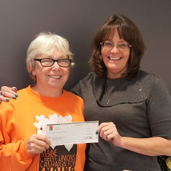 Brenda Davis (left) receives a donation from Maine Savings employee Amy Archer on behalf of the credit union at its office located at The Jackson Laboratory in Bar Harbor.