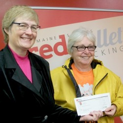 Brenda Davis (right) receives a donation from Maine Savings' Madolyn McAtee on behalf of the credit union at its Milo branch November 16.