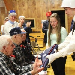 Demi Giroux and Ian West presenting flag from Senator Collins office to World War II Veterans Wallace Bisson and Leo Boudreau