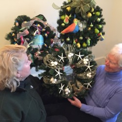 """Brett Turpin, Committee Member, and Marty Rogers, Senior Warden, admire three of nine unique wreaths to be part of silent auction at St Peter's Unique Boutique Holiday Shopping on November 19 from 9 a.m. to 3 p.m. at the church, 11 White Street, Rockland. From left to right, a """"sweet wreath"""" from Snow Drop Confectioners, a """"seascape"""" by Sea Gull Cottage, and a """"Partridge in a Pear Tree"""" by MABird Accessories."""