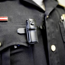 A stock photo depicts a traditional body camera worn by a police officer