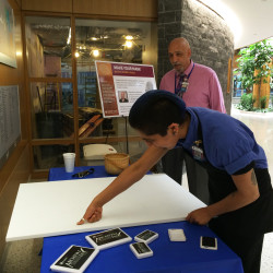 Artist Frank Manzo guides EMMC employee Liam Buenrostro, cafeteria attendant, Food and Nutrition, in placing the first thumbprint on canvas.