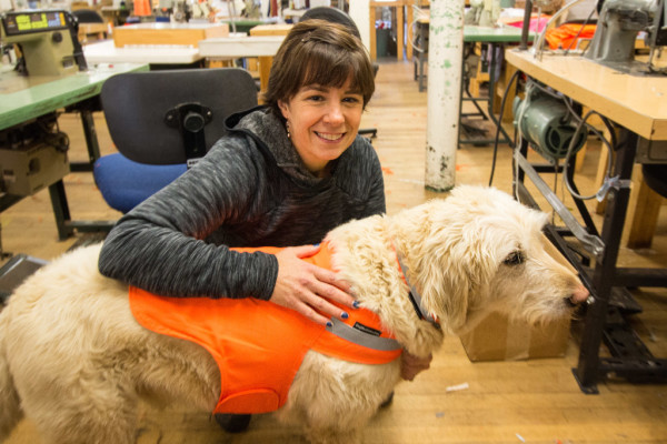 Julie Swain, co-owner and founder of Dog Not Gone, poses with her dog, Max, on Nov. 1, at Maine Stitching Specialties in Skowhegan, where Dog Not Gone products are manufactured. Dog Not Gone is a Kingfield-based company that creates and sells dog and human apparel and accessories that improve visibility while outdoors and repel ticks, mosquitoes and blackflies.