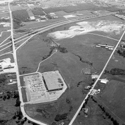 An aerial photo from 1977 shows initial work being done on site preparation for the Bangor Mall on Stillwater Avenue. The Kmart building, the first retail store built in the current mall area, is in the foreground.