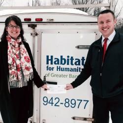 Matt Watkins of Bangor Savings Bank presents a check to Lynn Hempen of Habitat for Humanity of Greater Bangor.