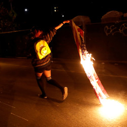 A demonstrator runs while holding a burning flag during a demonstration following the election of Donald Trump as President of the United States, in Oakland, California, Nov. 10, 2016.