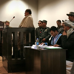 Abdulhai Jurat, a former military prosecutor accused of bribery, stands in the dock surrounded by police at his trial, one of the first in the new Anti-Corruption Justice Center in Afghanistan.