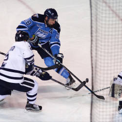 University of Maine's Will Merchant (second from left) tries to get the puck by University of New Hampshire goalie Danny Tirone (left) at the Cross Insurance Arena in Portland in this December 2015 file photo.