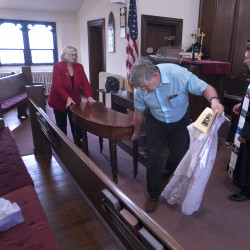 Rev. David Henry (right), pastor of First Baptist Church, looks on as First Baptist Church head usher Robert Staples (center) and another church member move the communion table after the Imago Dei Anglican Church service Sunday at the First Baptist Church building on Center Street in Bangor. The churches have been sharing space for over a month and intend to continue the arrangement for at least a year.