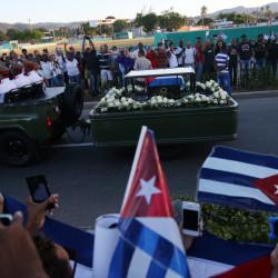 People watch the cortege carrying the ashes of Fidel Castro drive toward Santa Ifigenia cemetery in Santiago de Cuba on Dec. 4, 2016.