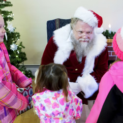 "Santa listens as Iyla Mitchell (right), 6, tells him what she wants for Christmas while Ella Dowing (left), 7, and Amelia Dowing, 2, wait their turn during the Festival of Lights in downtown Bangor Saturday. The theme this year was ""Holidays from around the World."""