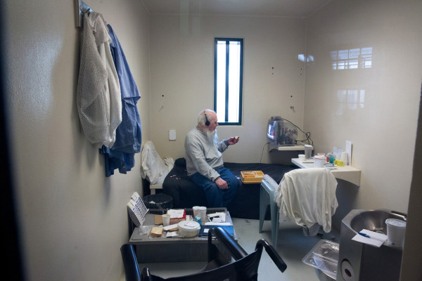 Albert, 82 years old, watches the news on television and eats his lunch at the Maine State Prison. Albert is the oldest inmate in Maine and one of four subjects in Jessica Earnshaw's Aging in Prison photo documentary.