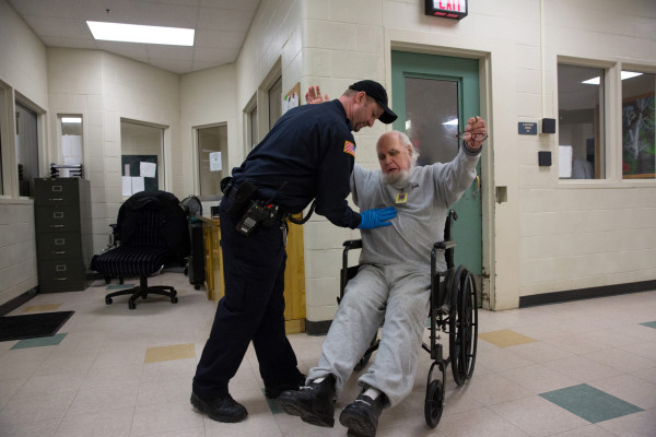 Albert, 82 years old, is patted down by security as he arrives to medical to get a blood test at the Maine State Prison. Part of Jessica Earnshaw's Aging in Prison photo documentary project, Albert is the oldest inmate in Maine.