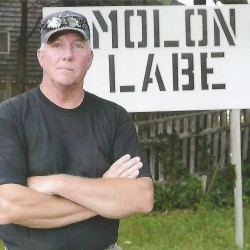 "Linc Sample of Boothbay Harbor, whose signs promoting the rights of gun owners have drawn criticism, recently removed a lighted sign featuring an assault weapon and replaced it with a simple nativity scene. Here, Sample stands in front of a sign, ""Molon Labe,' which means ""From my Cold Dead Hands."""