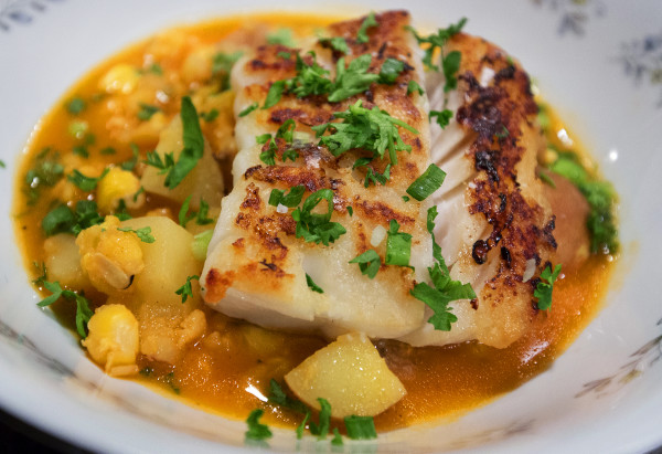 Roast cod in sweet pepper and crab broth with potatoes and hominy can be seen on Nov. 29 at Sammy's Deluxe in Rockland. The new restaurant focuses on Maine comfort food.